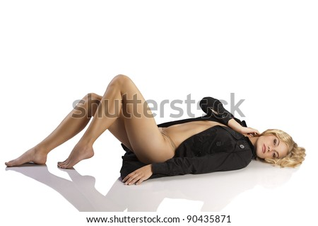 very sexy and young blond girl layng down on white wearing a black coat over her naked body - stock photo