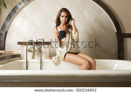 very sexy brunette model with black bikini and large floral shirt sitting in elegant retro rustic bathtub with long hair and sensual expression - stock photo