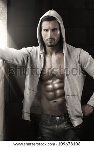 Very sexy male model with open jacket revealing muscular body and nice abs and chest - stock photo