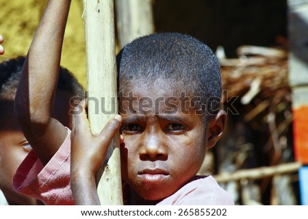 Very shy african boy with shadow on his face, poverty in Madagascar - stock photo
