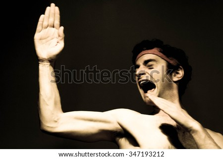 Very skinny headband wearing fighter shows skills - stock photo