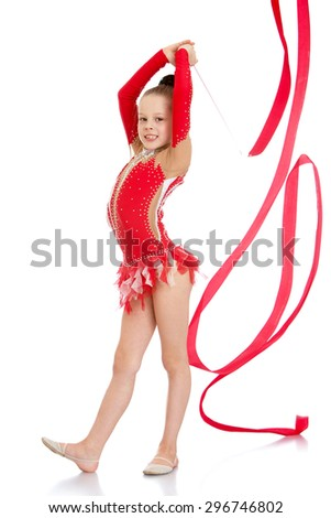 Very slender and beautiful young girl in a red bathing suits embroidered sequined perform exercises with the tape , the girl is engaged in gymnastics , she prepares to compete-Isolated on white - stock photo