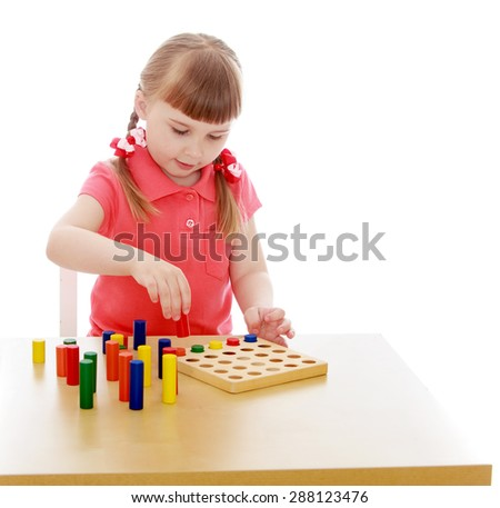 Very smart girl blonde in Montessori kindergarten playing in Montessori materials sitting at the table-isolated on white background