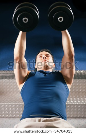 Very strong and handsome man lifting weights (dumbbells) in a gym - stock photo