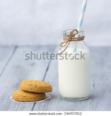 Very sweet retro bottle of milk with cookie on old table - stock photo