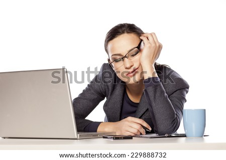 very tired business woman fell asleep leaning on her hand next to a laptop