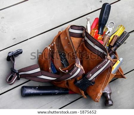 Very used tool belt on wood - stock photo