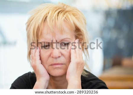 Very worried middle-aged woman - stock photo