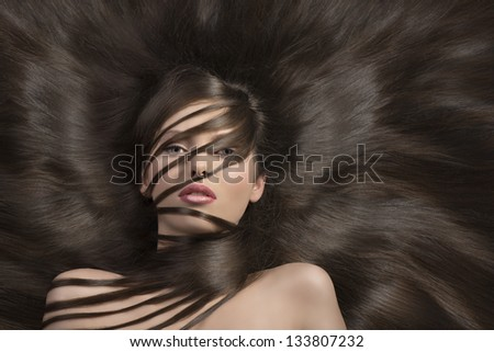very young and cute girl with long and creative hairstyle  laying down and some locks on the face and the neck - stock photo