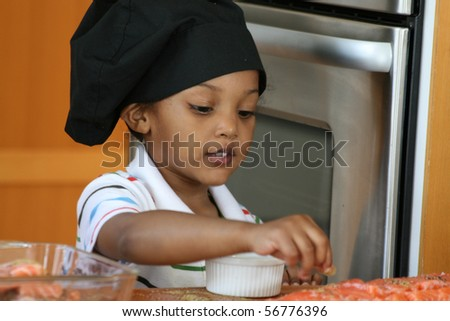 Very young chef adding spices and breading to salmon entrée. - stock photo
