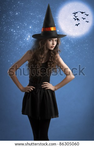 very young girl dressed as halloween witch posing under stars and moon wearing a huge witch hat - stock photo