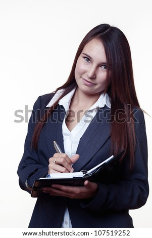 very young looking woman in a suit just starting out trying to do well in business taking notes in her filo fax - stock photo