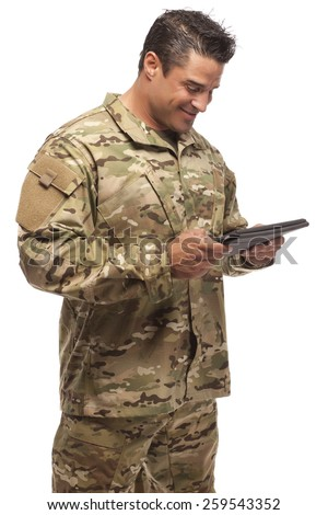 Veteran soldier | Happy army soldier looking down at digital tablet in front of white background