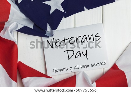 Veterans day 11th November. Veterans day. Honoring all who served. Printed on sheet of paper. American (USA) flag on wooden background.