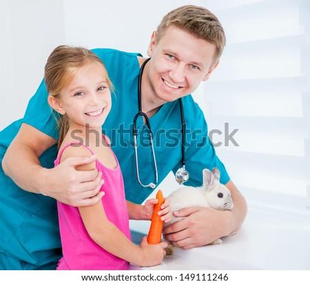 veterenarii and a happy little girl feeding rabbit carrot - stock photo