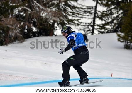 VEYSONNAZ, SWITZERLAND - JANUARY 22: World Champion Nate Holland (USA) in the  FIS World Championship Snowboard Cross finals : January 22, 2012 in Veysonnaz Switzerland - stock photo