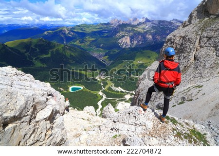 Via ferrata climber admires the landscape from Meisules plateau, Sella massif, Dolomite Alps, Italy - stock photo