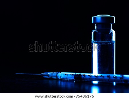 Vial and syringe with needle. Dark blue. MANY OTHER MEDICAL PHOTOS OF VIALS, SYRINGES ETC. IN MY PORTFOLIO - stock photo