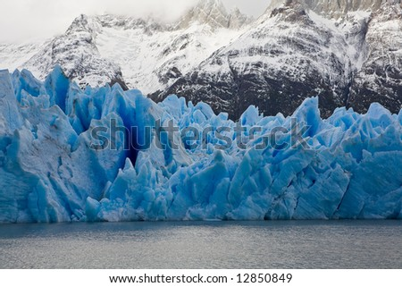 Vibrant blue icebergs in front of snowy mountains taken at Grey Glacier in Torres del Paine National Park, Patagonia. - stock photo