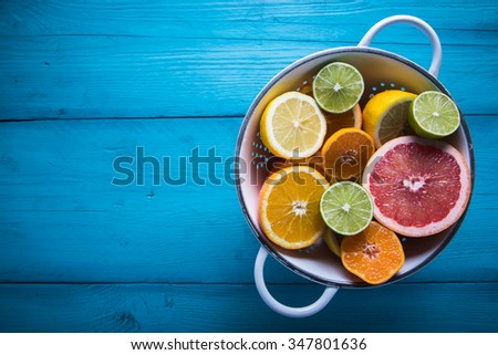 Vibrant citrus half cut fruits on wooden table - stock photo