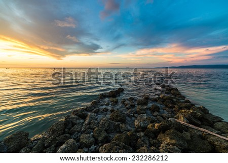 Vibrant colored cloudscape and dramatic seascape at dusk. Wide angle view from a stone waterbreak in Tanjun Karang, Central Sulawesi, Indonesia. - stock photo