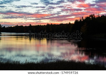 Vibrant colors of a cloudy, pre-dawn sky are reflected upon the peaceful and still waters of a lake in Michigan's Upper Peninsula. - stock photo