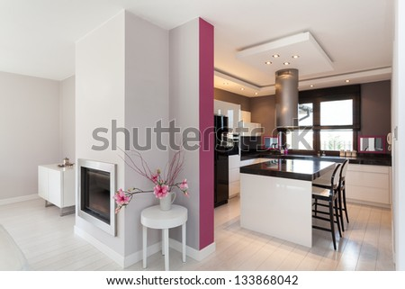 Vibrant cottage - kitchen and fireplace in living room - stock photo