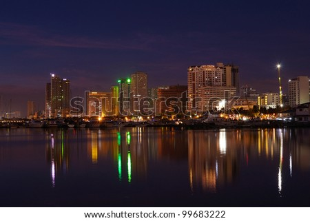 Vibrant Manila bay Philippines city nightscape and buildings water reflections. - stock photo
