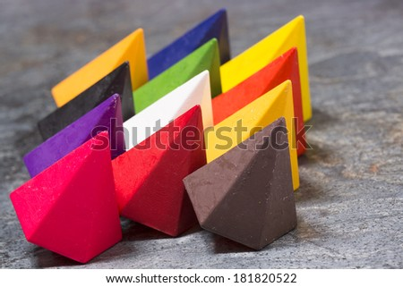 Vibrant multicolored diamond-shaped wax crayons in the colors of the rainbow arranged in three rows on a grey stone background, close up side view - stock photo