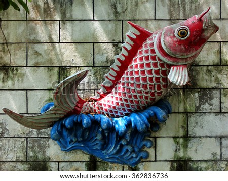Vibrant old koi fish statue on cement wall - stock photo