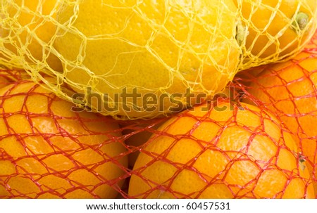 Vibrant Oranges and Lemons in plastic net bags from low perspective background. - stock photo