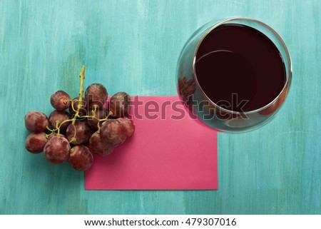Vibrant photo of glass of red wine with bunch of grapes and sheet of paper, shot from above on turquoise blue wooden background texture, with copyspace; template for tasting invitation