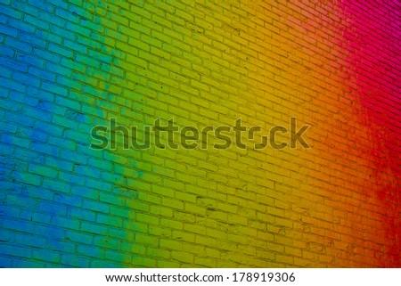 Vibrant rainbow colored brick wall shot from an angle - stock photo