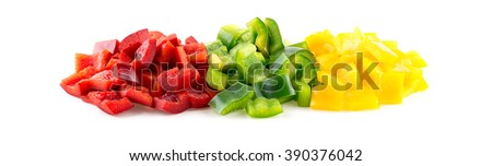Vibrant red, green and yellow capsicum peppers cut into pieces on white - stock photo