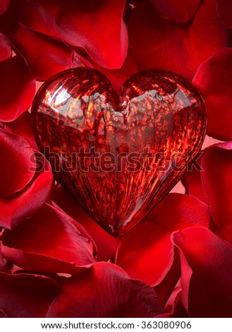 Vibrant red heart made of glass on a scarlet rose petals background