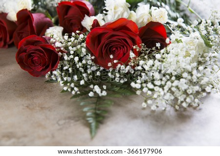 Vibrant red roses with baby's breath and white carnations for Valentine's Day. - stock photo