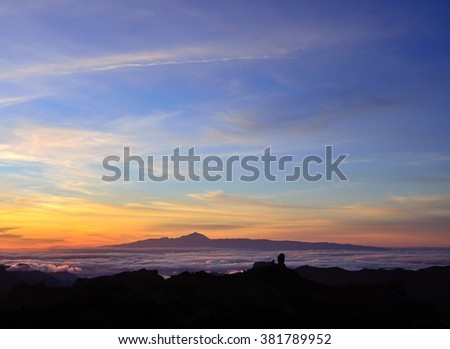 Vibrant sunset with Roque Nublo in foreground and Tenerife island in background, Canary islands  - stock photo