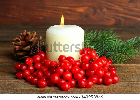 viburnum and lit the candle with a sprig of spruce on a wooden table - stock photo