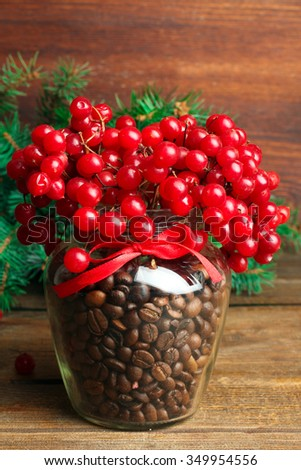 viburnum with coffee beans in a glass jar and fir twigs on wooden table - stock photo