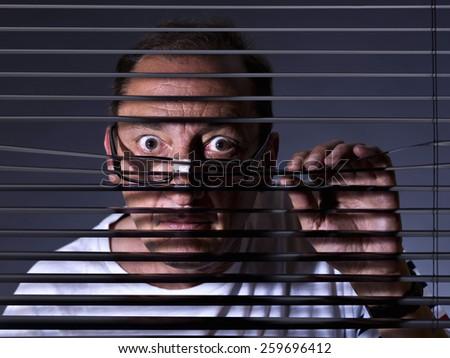 Vicious man looking sideways through venetian blind - stock photo