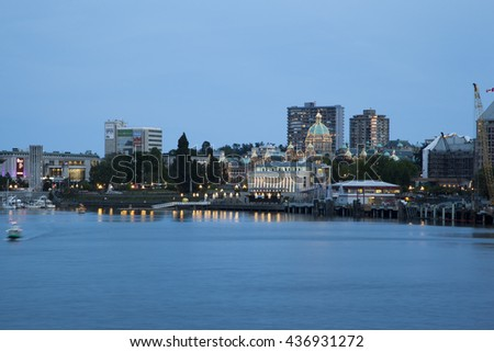 VICTORIA, BC, CANADA - MAY 17 2016: Night view of the Inner Harbor Downtown. Tourists strolling the causeway. This waterfront is the location of many tourist attractions and recreational activities. - stock photo