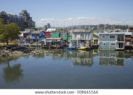 VICTORIA,CANADA-AUG 3,2016: Floating Home Village with colorful houseboats at Inner Harbor, Victoria, Canada. Area has floating homes, boats, piers, and restaurants.
