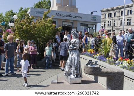 VICTORIA, CANADA -AUGUST 2, 2005: People looking at an actress in front of the Visitor Centre in the Inner Harbor. The actress wears an ancient dress,is painted in silver and looks like a sculpture. - stock photo