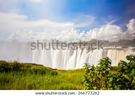 Victoria falls through through the mist and spray.  Blue sky and green grass in the foreground. - stock photo