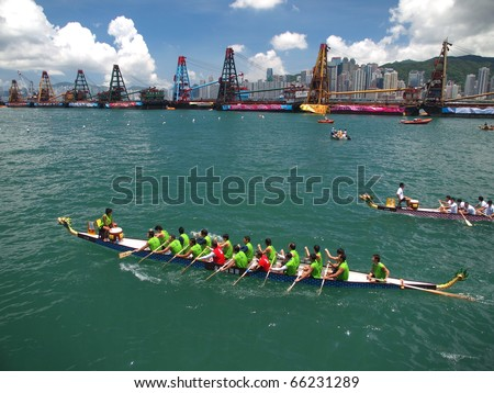 VICTORIA HARBOUR, HONG KONG - JULY 24: Participants paddle their boats during a dragon boat race on July 24, 2010 in Victoria Harbour, Hong Kong - stock photo