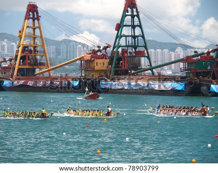 VICTORIA HARBOUR, HONG KONG - JULY 24: Unidentified participants paddle their boats during a dragon boat race on July 24, 2010 in Victoria Harbour, Hong Kong - stock photo