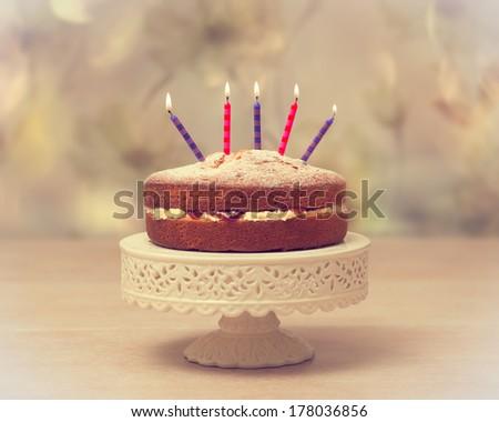Victoria sponge Birthday cake with lit candles - antique vintage tone effect added - stock photo