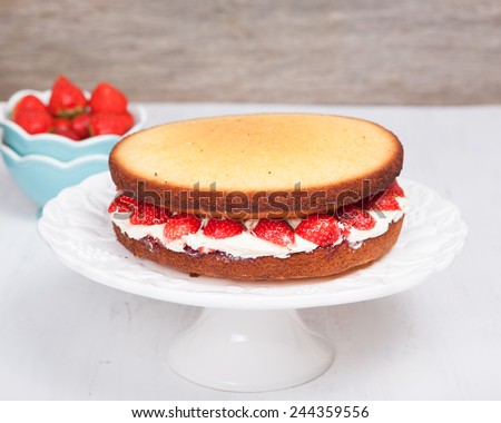 Victoria sponge cake with buttercream frosting, jam and strawberries on the stand, selective focus - stock photo