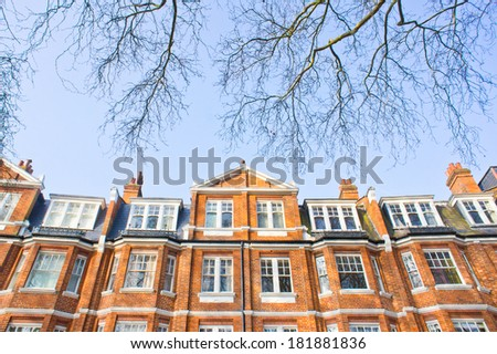 Victorian architecture in London with blue sky and tree branches - stock photo