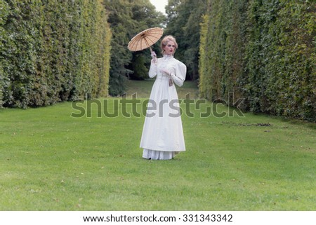 Victorian fashion woman holding parasol standing on lawn with tall hedge. - stock photo